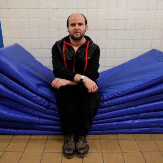 Shelter_man sitting on mats